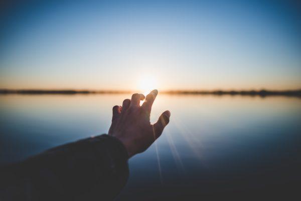 太陽を手で捕まえようとする写真